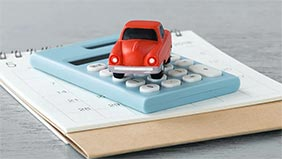Red toy car on a calculator