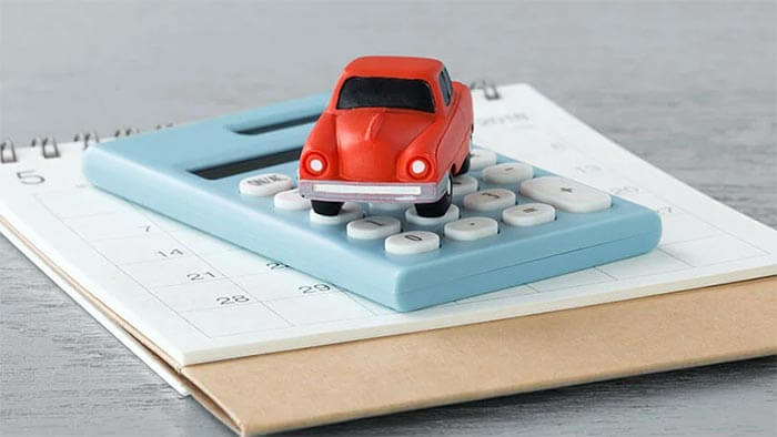 A red toy car on a calculator