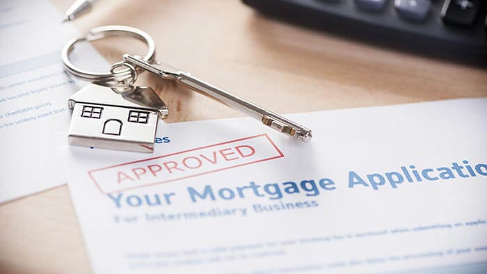 An approved mortgage application with a set of house keys in the foreground