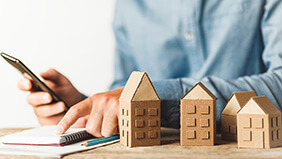 Person calculating their finances with wooden houses in the foreground