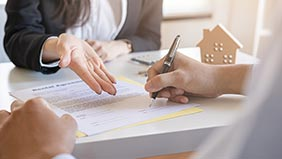 Close up of a hand signing a mortgage agreement while a lender gestures at the paper.