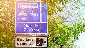 Bus lane sign showing times of operation and warning that cameras are active