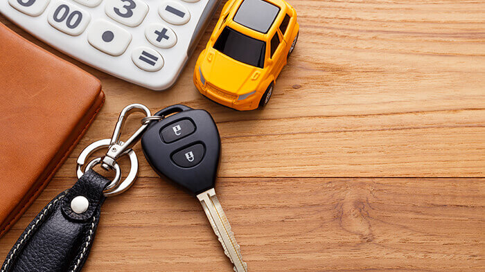 keys on table with a calculator and toy car