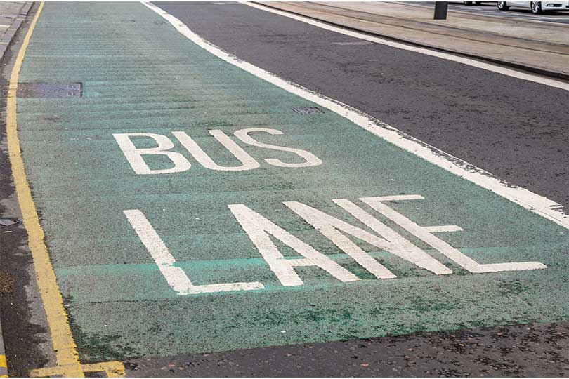 Faded bus lane painted on a road