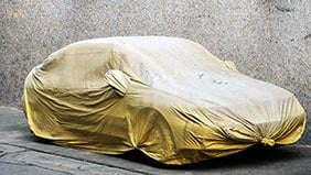 A car covered in a heavy yellow cloth