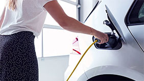 Woman plugging in an electric car charge plug.