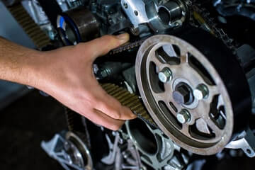Mechanic changing the timing belt on a car