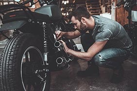 Mechanic making repairs on a motorbike