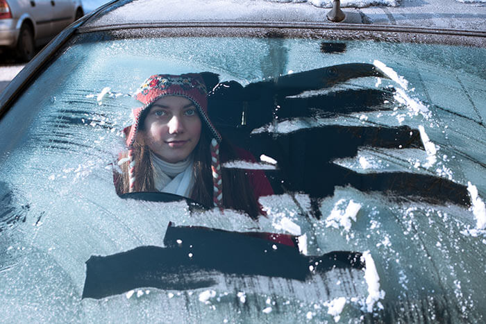 Woman sat in her car while there's ice on the windscreen and there's a porthole of clear glass