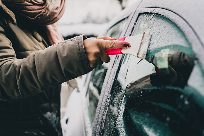 Woman scraping ice off a car window with an ice scraper.