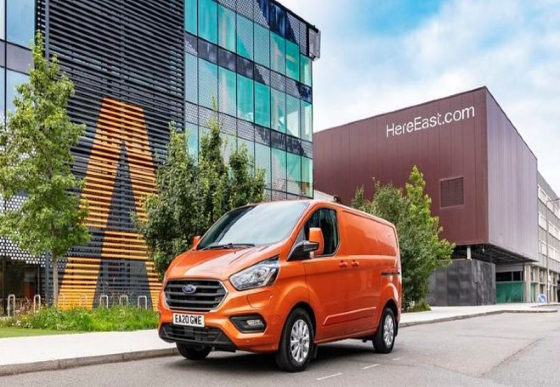 An orange ford transit on the road