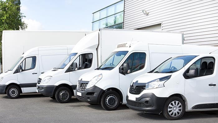 A fleet of white vans in a line, all of different body types