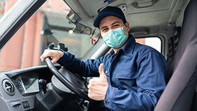 Van driver wearing mask giving the thumbs up