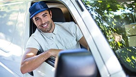 Van driver wearing a hat leaning out the window and smiling