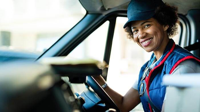 Courier in van wearing blue uniform and hat, smiling