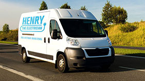 "A white van with ""Henry the Electrician"" written across the side"