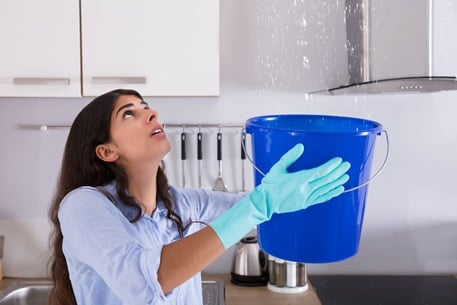woman holding a bucket for leak